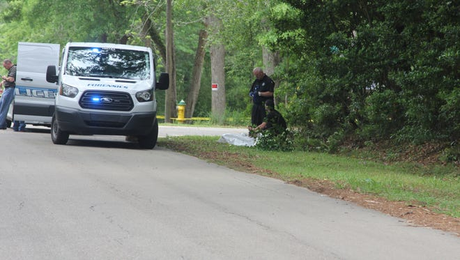 Tallahassee Police Department investigators work a crime scene at the corner of Pecan and Willie Vause roads where a body was found Saturday morning.