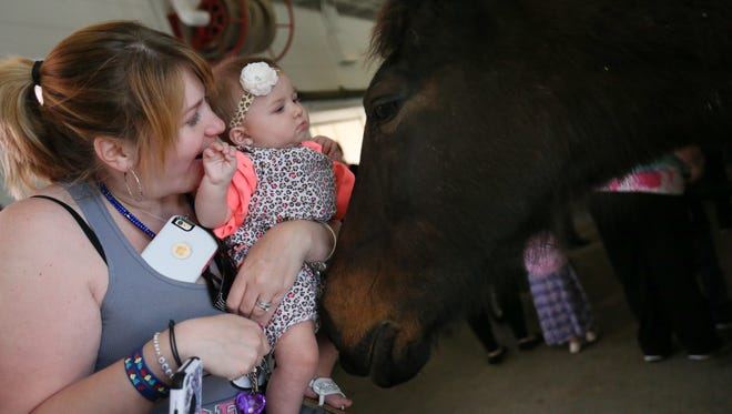 Six-month-old Raelynn Leach and Jennifer Graham meet Miss Cutie at the Country Spring Festival at Carousel Park Saturday in Pike Creek.