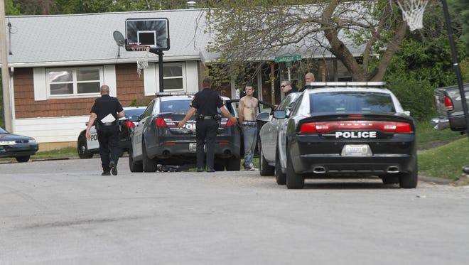 Police questioning the suspect who came out of the house after a standoff.