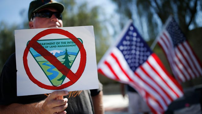 David Andersen, of Overton, Nev., holds a sign during a rally in support of rancher Cliven Bundy outside of the federal courthouse Friday, April 22, 2016, in Las Vegas.