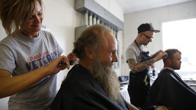 Allen Gerrell, an Air Force veteran from 1973-79, has his hair cut by Becky Starling during the North Florida Homeless Veterans Stand Down event at the fair grounds on Friday.
