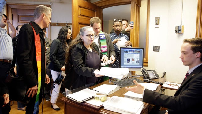 Gay-rights supporters add to a stack of over 4,000 petitions against a proposed constitutional amendment delivered to the office of House Speaker Todd Richardson Thursday, March 31, 2016, in Jefferson City, Mo. The amendment, which would protect some businesses citing religious objections while denying goods or services related to same-sex weddings, passed the Senate after a failed 37-hour filibuster by Democrats and now needs House approval before it can be put on a ballot this year. (AP Photo/Jeff Roberson) Thursday, March 31, 2016, in Jefferson City, Mo. A proposed constitutional amendment to protect some businesses citing religious objections while denying goods or services related to same-sex weddings passed the Senate after a failed 37-hour filibuster by Democrats and now needs House approval before it can be put on a ballot this year. (AP Photo/Jeff Roberson)