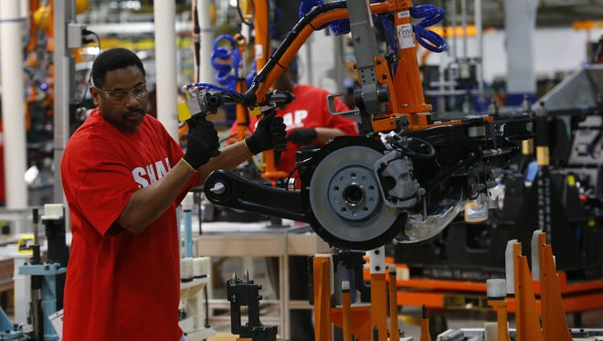 An assembly line worker builds a 2015 Chrysler 200 automobile at the Sterling Heights Assembly Plant in Sterling Heights, Mich., Friday, March 14, 2014. (AP Photo/Paul Sancya)