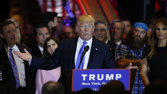 Republican frontrunner Donald Trump speaks at Trump Tower in New York on April 26,2016 after winning primaries in Pennsylvania, Maryland, Connecticut, Rhode Island and Delaware. At left is New Jersey Governor Chris Christie. / AFP PHOTO / KENA BETANCURKENA BETANCUR/AFP/Getty Images