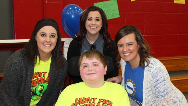 Carter Juedes, younger brother of Jonah Juedes, who died of Muscular Dystrophy, poses with MDA staff members, from left, Heather Buchberger, Lauren Nelsen and Sarah Arndt. Carter has the same condition as his brother.