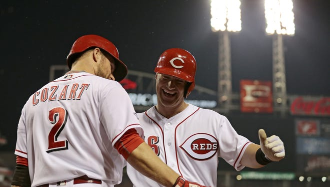 Cincinnati Reds shortstop Zack Cozart (2) cheers on catcher Tucker Barnhart (16) as he heads back to the dugout after his go-ahead solo home run in the bottom of the seventh inning of the MLB National League game between the Cincinnati Reds and the Pittsburgh Pirates at Great American Ball Park in downtown Cincinnati on Monday, May 9, 2016.