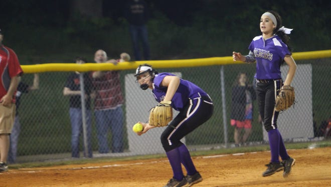 Clarksville High third baseman Taylor Adkins scoops up a ground ball bare-handed and throws out a Henry County batter at first base during the sixth inning of their District 10 softball tournament game Friday night.