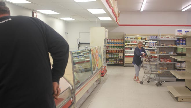 Shoppers and store personnel peruse the shelves at the new Freeman Foods in North English.