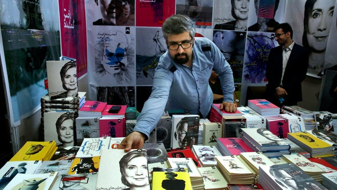 "In this picture taken on Tuesday, May 10, 2016, a book seller arranges US presidential candidate Hillary Clinton's book ""Hard Choices"" translated to Persian during Tehran's International Book Fair in Iran. Iranians have some concerns about Democratic frontrunner Clinton, who many consider to have struck a relatively hard line on Iran during her time as Secretary of State."