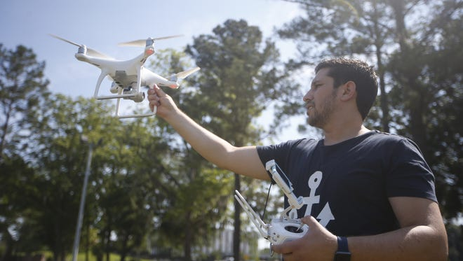 Alex Workman, who started Aerial Tallahassee with his wife Chelsea, corals one of the unmanned aerial vehicles the couple uses to document the city from above.