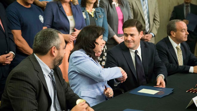 Secretary of State Michele Reagan shakes hands with Gov. Doug Ducey.