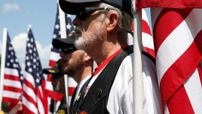 Philip Gerrell of the Patriot Guard Riders holds a flag along the outside of the Tallahassee National Cemetery Memorial Day ceremony on Sunday.