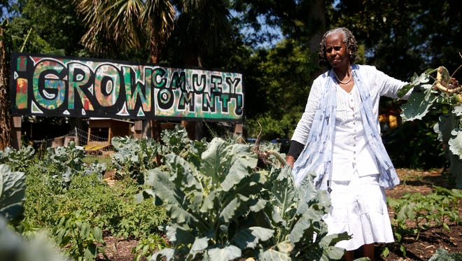 Miaisha Mitchell, a cofounder of IGrow farm, works with volunteers Monday to pull collard greens from the vegetable beds.
