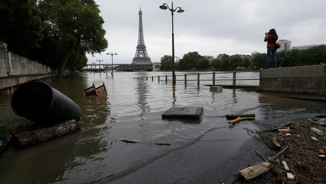 A woman takes photos of the flooded banks of the Seine river in Paris, France on June 4, 2016.