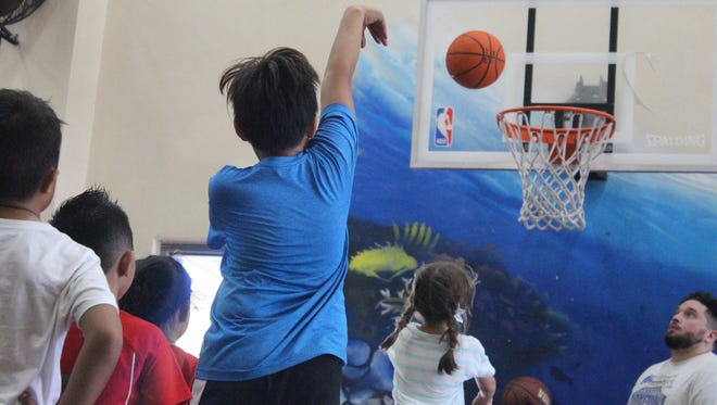A summer camp participant from iFit Guam Sports Center make a shot during a workshop conducted by Nothing But Net Guam.