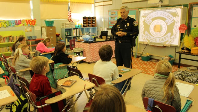 Police Capt. Billy Morgan discusses safety measures with elementary school students at Morgan Academy in Selma.