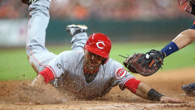 Cincinnati Reds second baseman Jose Peraza (9) slides home safely to score a run during the fifth inning against the Houston Astros at Minute Maid Park.