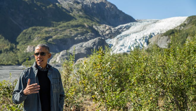 In this Sept. 1, 2015 file photo, President Barack Obama speaks to members of the media while on a hike to the Exit Glacier in Seward, Alaska. After an emotionally trying week, the president is heading West to celebrate the raw beauty of America's national parks as the system nears its 100th birthday, and highlight challenges threatening it over the next 100 years, including climate change and chronic underfunding by Congress. Obama was taking his wife and daughters on a Father's Day weekend getaway to Carlsbad Caverns National Park in New Mexico and Yosemite National Park in California. (AP Photo/Andrew Harnik, File)