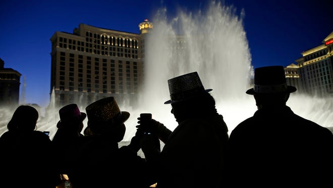 In this Dec. 31, 2015, file photo, people watch the fountains at the Bellagio while wearing paper hats to celebrate New Years Eve in Las Vegas.