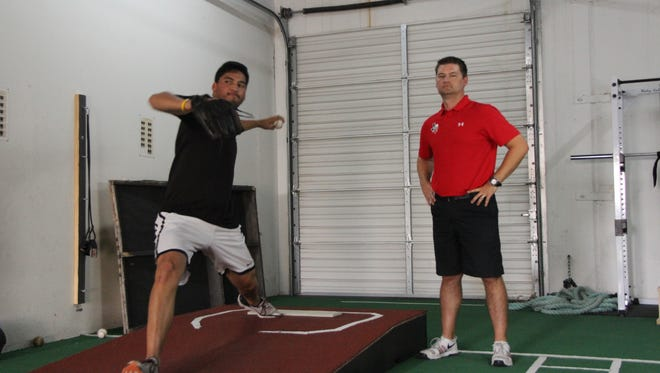 Andy Powers, right, trains a client at the Texas Pitching Institute in West El Paso.
