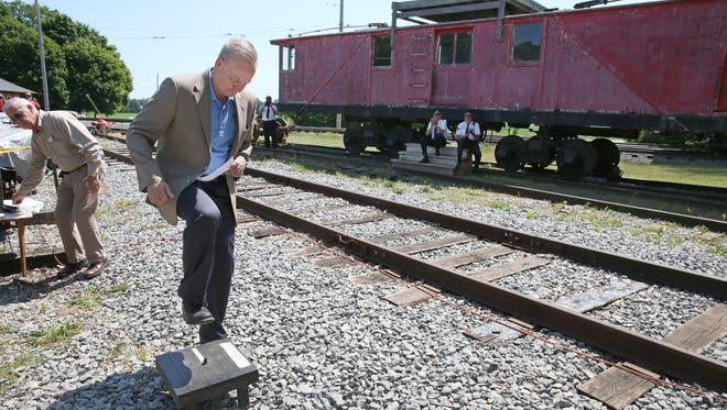 """Bill Carpenter, RTS Chief Operation Office, does the honors of signaling the opening of the doors for the """"Casey Jones"""" on it's christening run down track 23 at the New York Museum of Transportation in Rush  Saturday, June 25, 2016.  Carpenter is stomping on a Brass Trolley Gong that makes a loud bell ringing sound."""