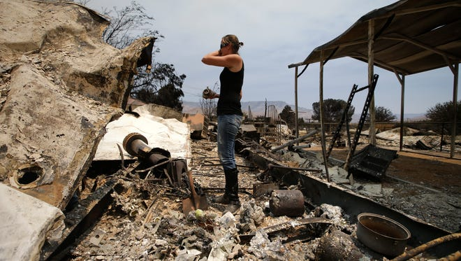 """Amy Nelson, 30, breaks down as she goes through the remains of her home devastated by a wildfire Saturday in South Lake, Calif. """"I didn't think it was going to be this bad,"""" said Nelson."""