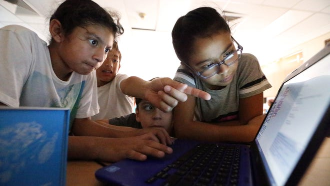 Keoni Overa, left, and sister Laurencia Olvera, right, work on programming a robotic vehicle model at an mBot STEM summer camp.