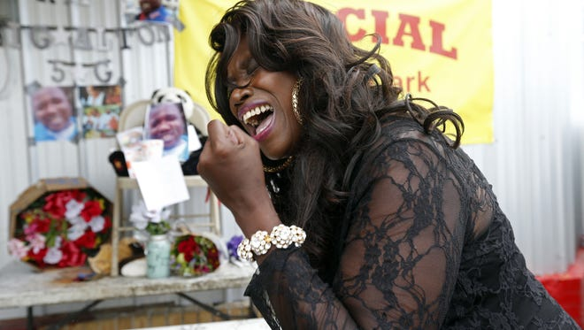 Stephanie McDee, who said she is a local blues singer, sings a song and protests at a makeshift memorial for Alton Sterling, outside a convenience store in Baton Rouge, La., Wednesday, July 6, 2016.   Sterling was shot and killed by Baton Rouge police outside the store where he was selling CDs. (AP Photo/Gerald Herbert)