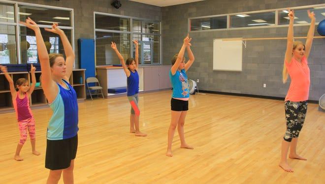 Southern Utah ballroom dancer Emily Burton teaches beach-themed dance moves to girls during the summer.