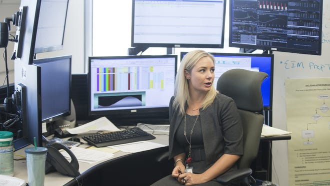 Jessica Kelsey, real-time trader, works at the power desk and outputs from generators at APS headquarters on June 27, 2016, in Phoenix.