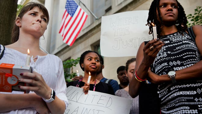 Ashley Wilson, 21, left, a student at George Washington University, Janay Richmond and Jeanne Isler, right, both with the National Committee for Responsive Philanthropy, rally in support of the 'Black Lives Matter' movement in front of the Department of Justice in Washington on Friday.