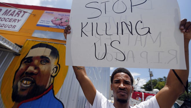 A man holds a sign in front of a mural of Alton Sterling in front of the Triple S Food Mart in Baton Rouge during a July 7 protest of the shooting of Sterling, 37.