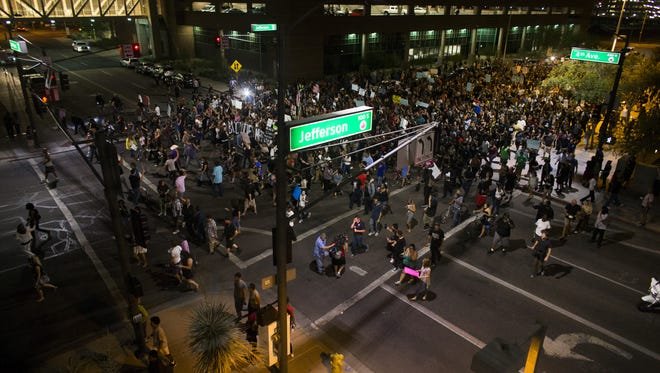 People chant as they walk during a protest march past Phoenix City Hall on July 8, 2016 in Phoenix, Ariz.