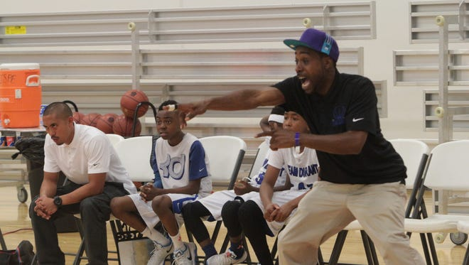 Team Durant coach Kareem Saunders points out instructions to his team as they compete in an AAU Boys 10U tournament pool play game Sunday at the Clarksville Christian School gym.