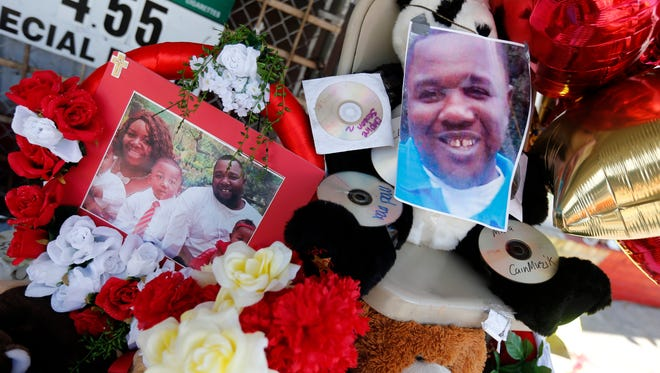 Photos of Alton Sterling are interspersed with flowers and mementos at a makeshift memorial in front of the Triple S Food Mart in Baton Rouge, La., Thursday, July 7, 2016. Sterling, 37, was shot and killed outside the convenience store by Baton Rouge police, where he was selling CDs. (AP Photo/Gerald Herbert)