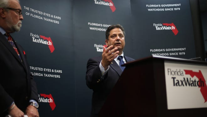 President and CEO of Florida TaxWatch Dominic Calabro speaks, while Barney Bishop, president of NEBA and chair of Citizens for Responsible Spending stands at his side, during a news conference releasing new poll results on city spending.