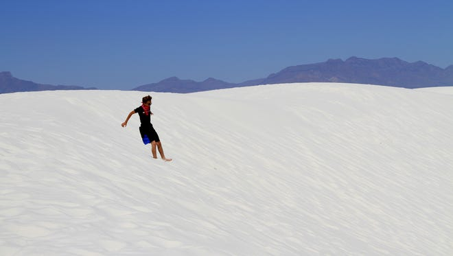 In this May 2016 file photo, a White Sands National Monument visitor slides down a dune at the monument. Otero Commissioners are discussing the possibility of White Sands becoming a national park.