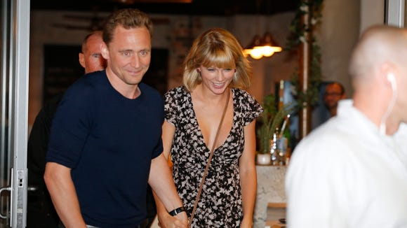 Tom Hiddleston and Taylor Swift leave a restaurant