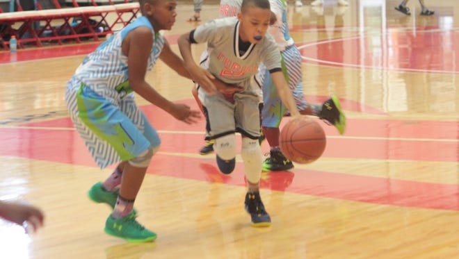 Baltimore Team Thrill's J'Lin Brown dribbles past a Nightrydas Elite defender during their AAU Boys 10U championship title game Wednesday at Austin Peay's Dunn Center.