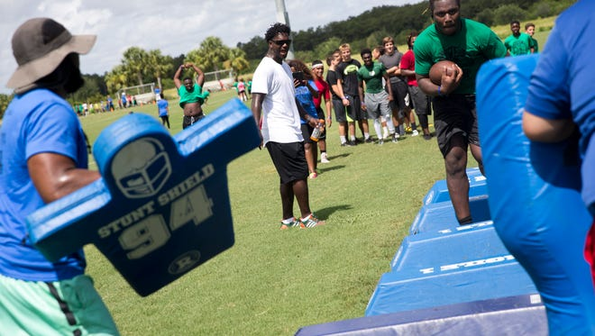 Edgerrin James, center, watches as Abraham Alce carries the ball through a running drill during the 7th Annual Edgerrin James Football Skills Camp at North Park in Ave Maria, Fla. Monday, July 18, 2016. The Immokalee High School product and former NFL all-pro running back hosts the free camp for kids, ages 6-18, to offer help with mechanics, leadership, and teamwork.