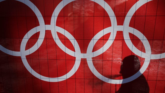 In this Feb. 15, 2014 file photo the shadow of a man is cast on the Olympic rings as he smokes at the Rosa Khutor Alpine Center, at the 2014 Winter Olympics in Krasnaya Polyana.