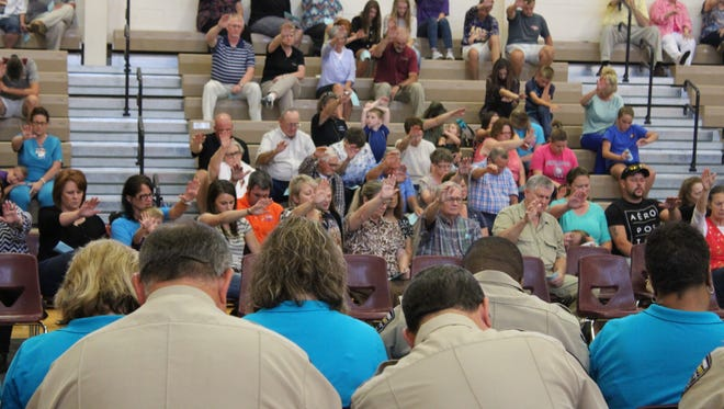 Grant Parish residents reach out in prayer for law enforcement officers (seated) on Thursday at Grant Junior High School.