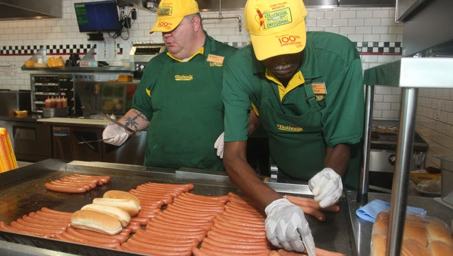 Joseph Downing, left, and Leslie Johnson cook hot dogs on Saturday at Nathan's Famous in Fort Myers.