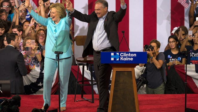Hillary Clinton raises her arms with her vice presidential running mate, Sen. Tim Kaine, after speaking at a campaign rally at Florida International University in Miami on Saturday, July, 23, 2016. The rally was the first public appearance of Kaine after being named Clinton's running mate.