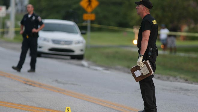 An officer marks evidence as police close off the intersection of Georgetown Road and 71st. Street, Monday July 25th, 2016. Authorities were on scene after a police chase ended with an officer shot in the lower extremities, another officer received minor injures, and a suspect  shot and killed.