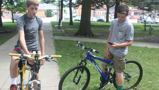 Nick Marovets (left), 14, and Brody Wardenburg, 13, both of Williamsburg, check their Smartphones for the location of special treasures and bonus items with the new Pokemon Go game. The new game, launched earlier this month, has created a worldwide sensation.