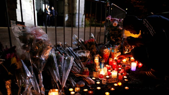 A man lits a candles at a makeshif memorial in front of the Saint-Etienne du Rouvray church on July 27, 2016, after the priest Jacques Hamel was killed on July 26 in the church during a hostage-taking claimed by Islamic State group.
