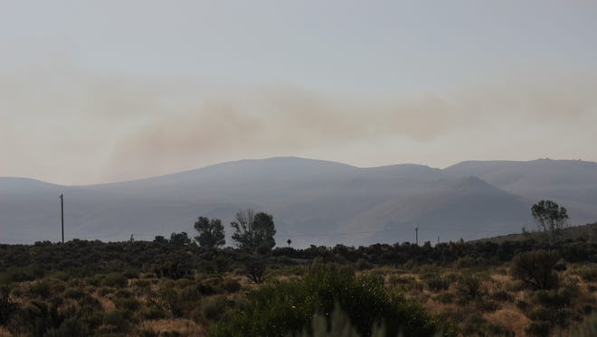 Smoke from the Rock Fire hangs over the desert north of Reno on Friday, July 29, 2016.