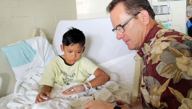 "While touring Guam Memorial Hospital Tuesday morning, acting Gov. Ray Tenorio takes a moment to read the Dr. Seuss story ""A Fly Went By"" to pediatric patient Carl Dorion, 7."