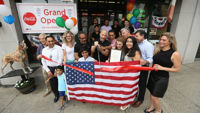 Mayor of Boonton, Matthew DiLauri, center, helps cut the ribbon with owner Mickey Chopra as Vinnie's Pizzeria & Ristorante celebrates its grand opening on Main Street in Boonton. August 5, 2016, Boonton, NJ